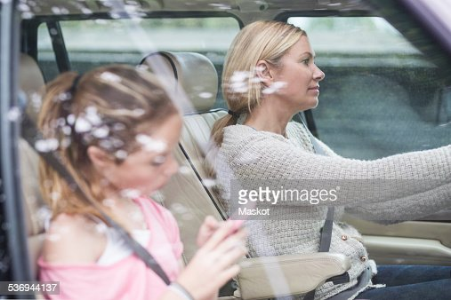 Woman driving while daughter using mobile phone in car