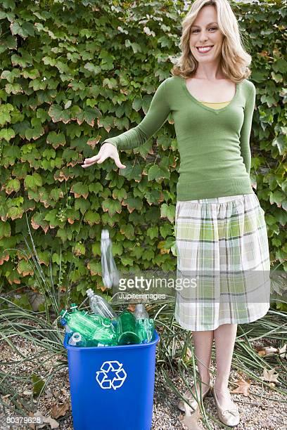 Woman dropping bottle into recycling bin