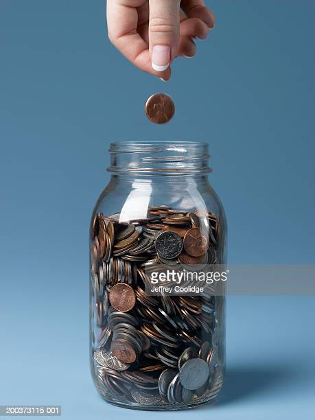 Woman dropping coin into jar close-up