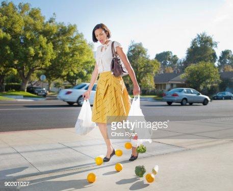 Woman dropping groceries on sidewalk : Stockfoto