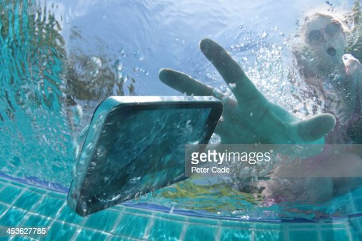 Swimming Pool Identification : Woman dropping phone into swimming pool stock photo