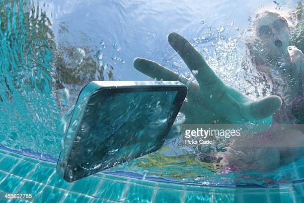 Woman dropping phone into swimming pool