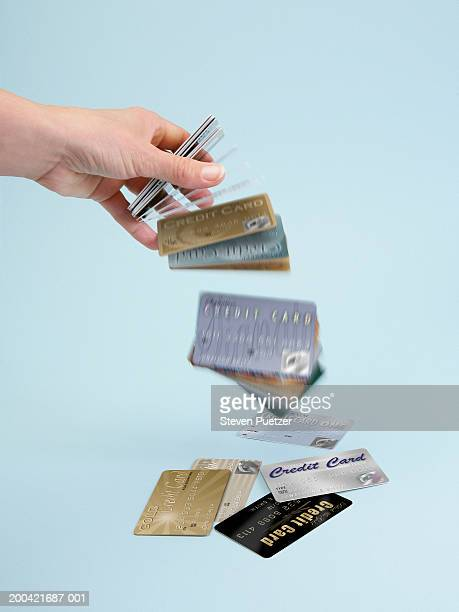 Woman dropping stack of credit cards (focus on hand)