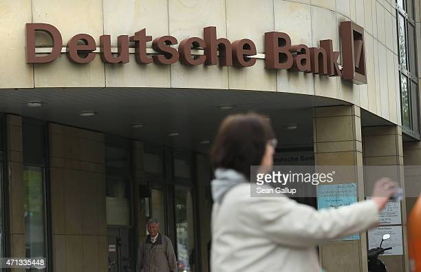 A woman drops refuse into a trash can next to a branch of German bank Deutsche Bank on April 27 2015 in Berlin Germany Deutsche Bank announced...