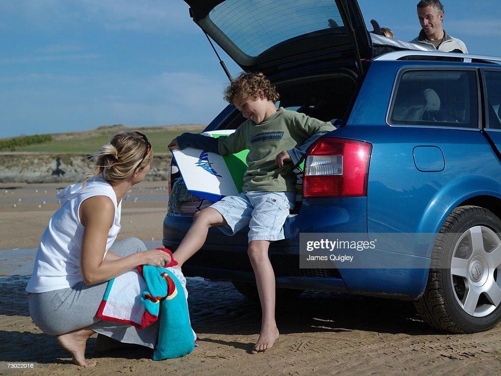 Woman drying feet of boy (7-9) at beach