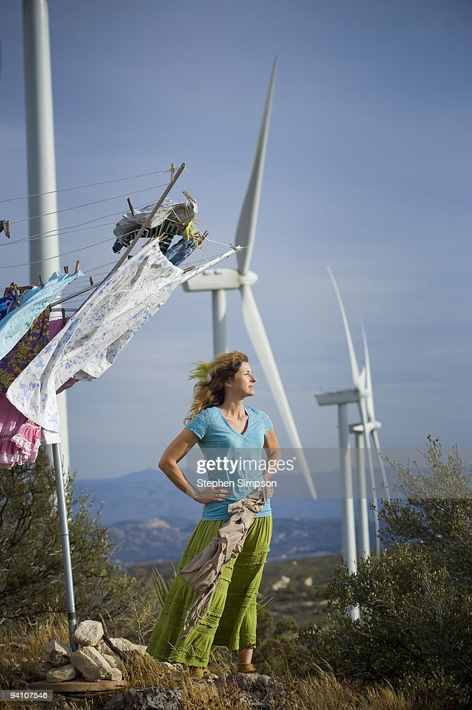 woman drying laundry by wind turbines : Stock Photo
