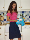 Woman drying plates in kitchen