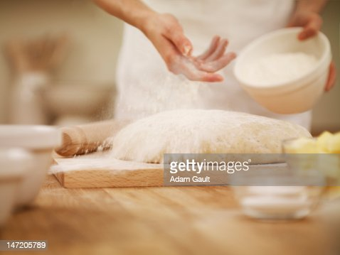 Woman dusting dough with flour