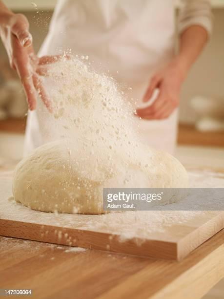 Woman dusting dough with flour