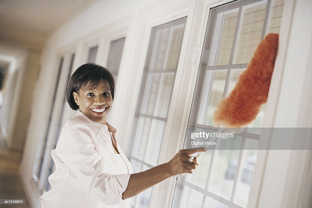 Woman Dusting Windows of Domestic Interior : Stock Photo