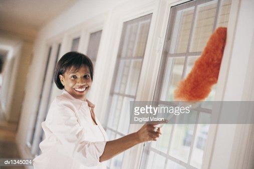 Woman Dusting Windows of Domestic Interior