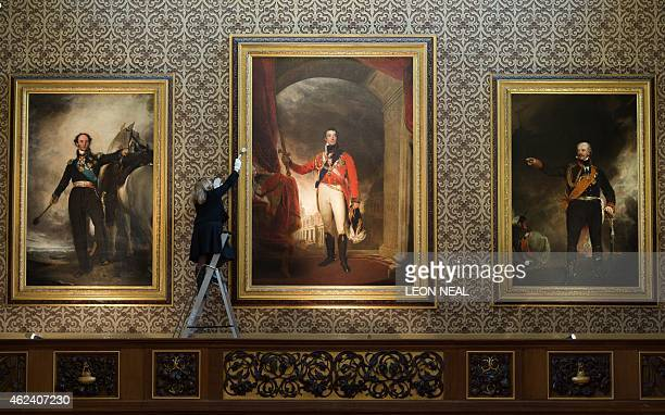 A woman dusts the frame of a painting of Arthur Wellesley Duke of Wellington by British artist Thomas Lawrence flanked by a portrait of of Russian...