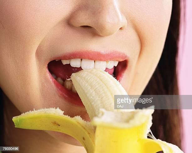 A Woman Eating a Banana, Front View, Close Up