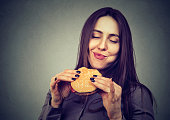 woman eating a big hamburger, isolated on gray background