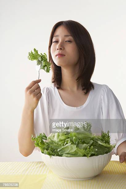 Woman eating a large bowl of salad