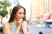 Pensive happy woman sipping a milkshake in the street