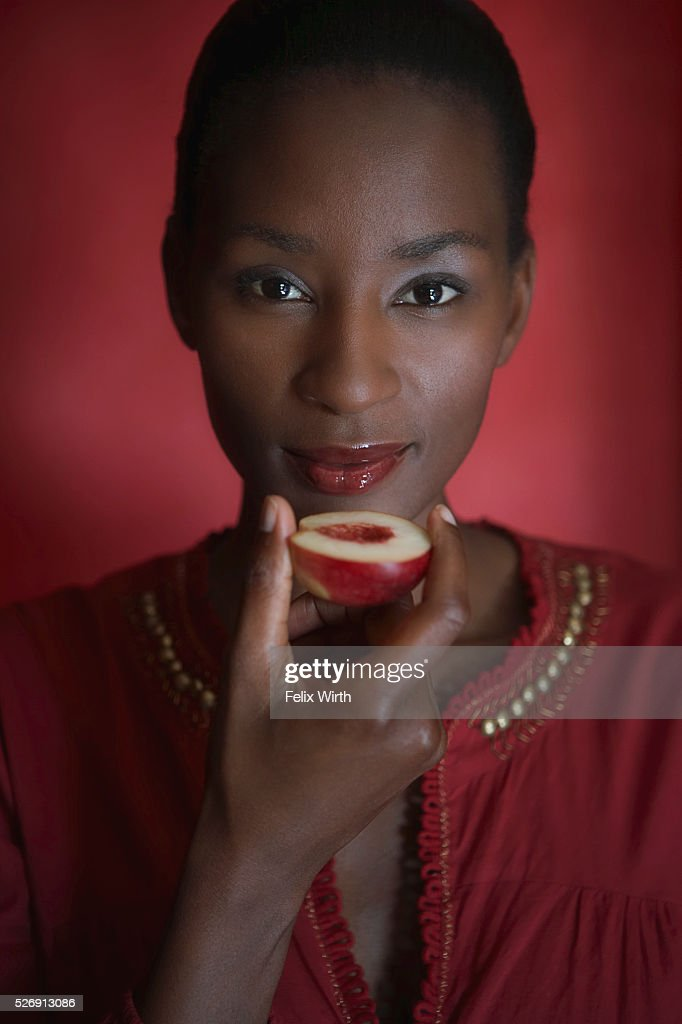 Woman eating a peach : Stock Photo
