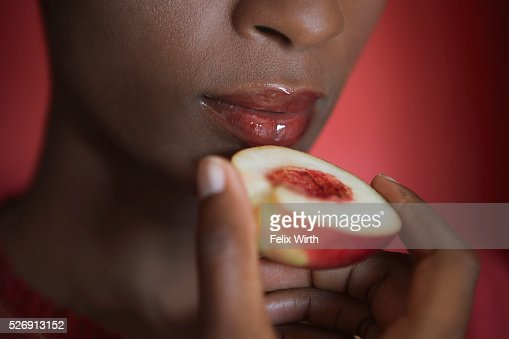 Woman eating a peach : Stockfoto