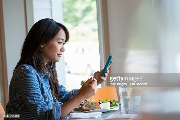 A woman eating a salad, and checking her phone.