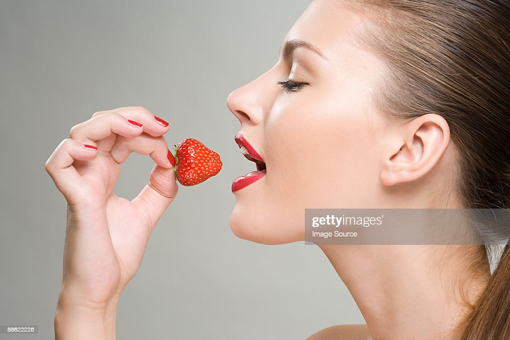 A woman eating a strawberry