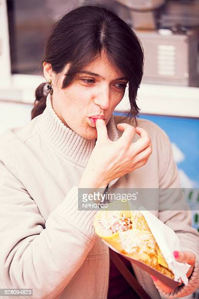 Woman eating a tasty crepe