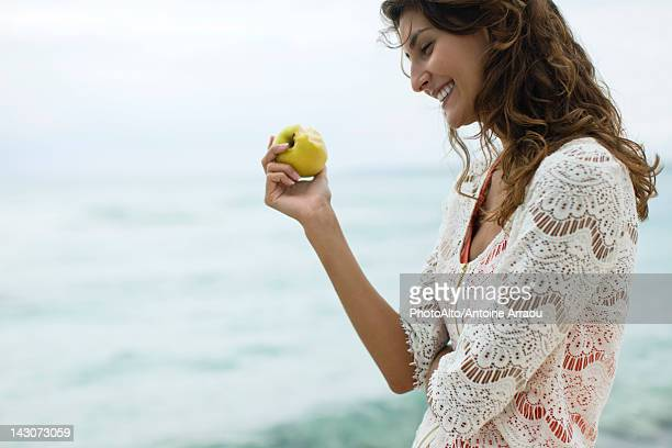 Woman eating apple at the beach