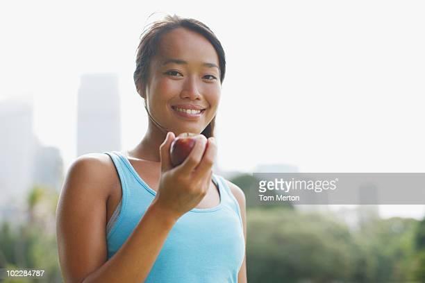Woman eating apple in urban park