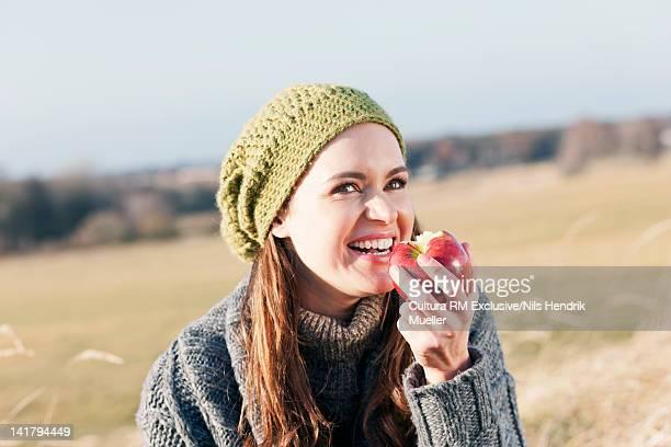 Woman eating apple in wheatfield