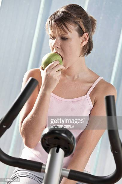 Woman eating apple on exercise machine
