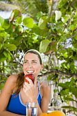 Woman eating apple outdoors
