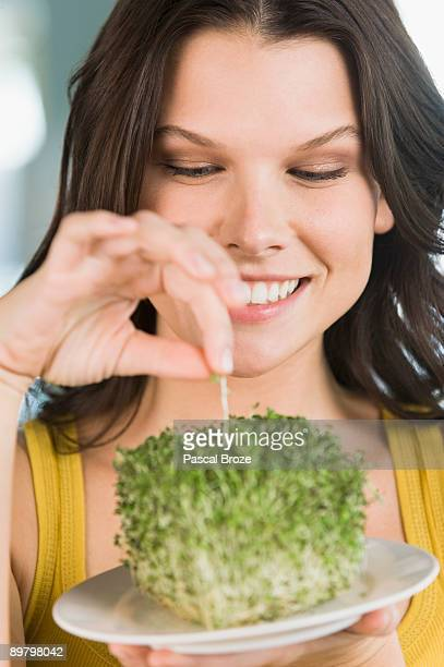Woman eating bean sprouts and smiling