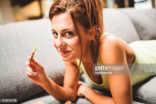 Donna mangiare biscuit e rilassante sul divano