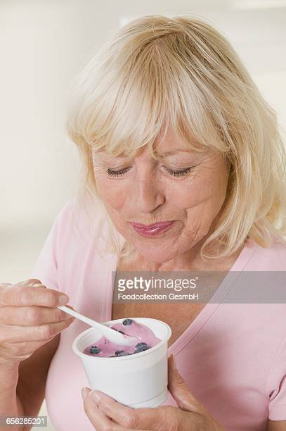 Woman eating blueberry yoghurt