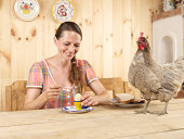 Woman eating boiled egg with chicken on table