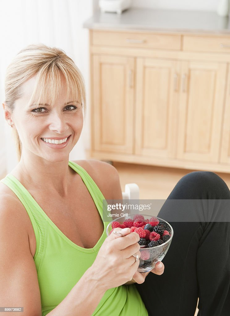 Woman eating bowl of berries, smiling : Stock Photo
