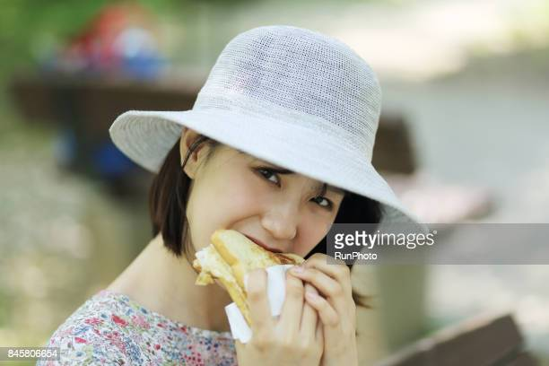 woman eating bread while watching the camera