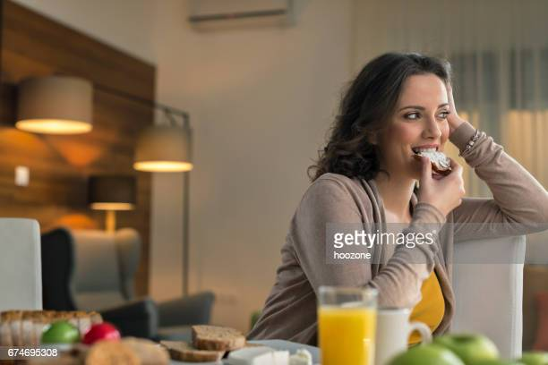 Woman eating bread with cream cheese