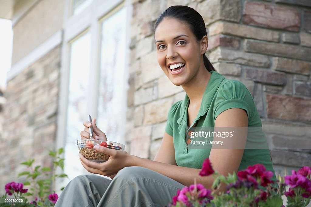 Woman eating breakfast outdoors : Stock Photo