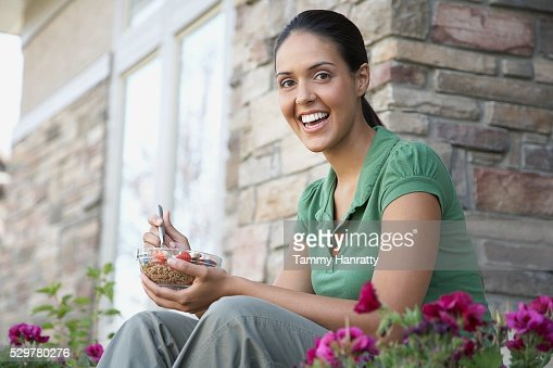 Woman eating breakfast outdoors : ストックフォト