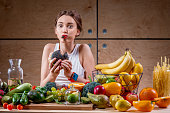 Hungry woman eating black burger at the table full of fruits and vegetables on the wooden background. Choosing between healthy and unhealthy food