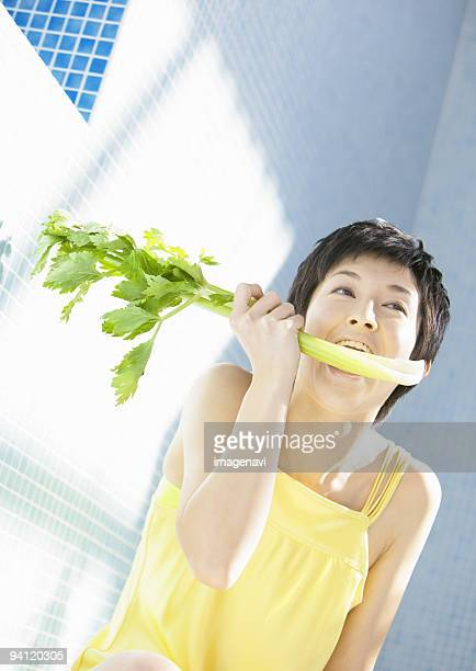 A woman eating celery