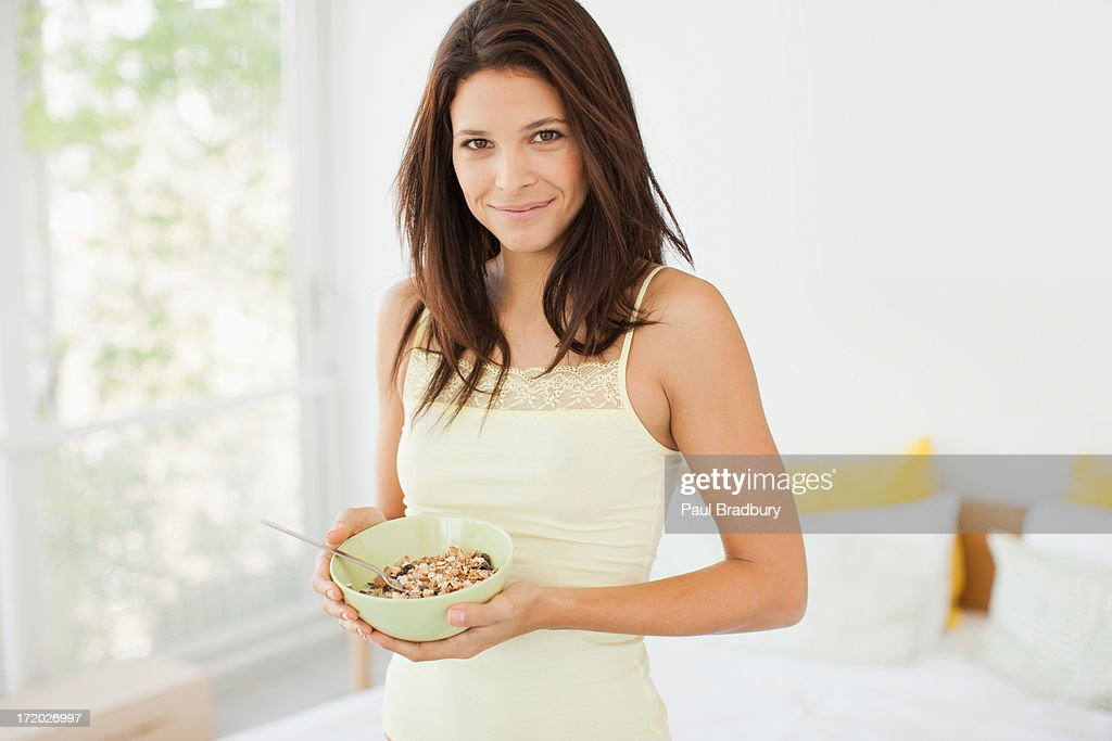 Woman eating cereal in bedroom : Stock Photo