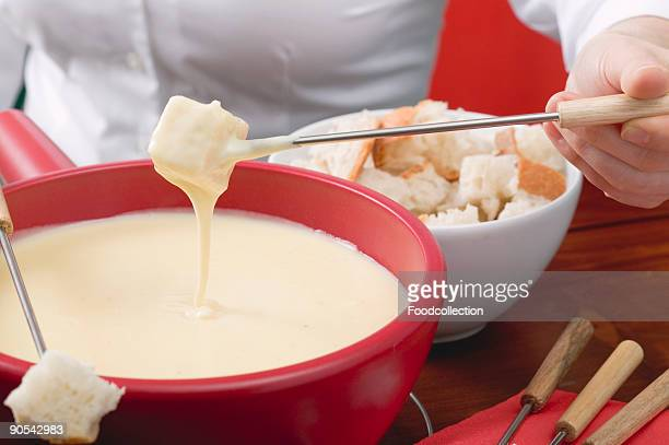Woman eating cheese fondue, close up