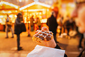 Woman eating traditional waffles with hazelnut chocolate creme at oldest Christmas Market worldwide in central Strasbourg, Alsace with market stalls in the background