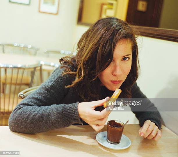 Woman eating churros with chocolate