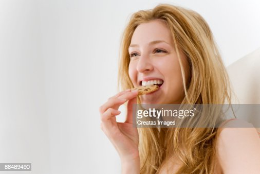 Woman eating cookie in bed : Stock Photo