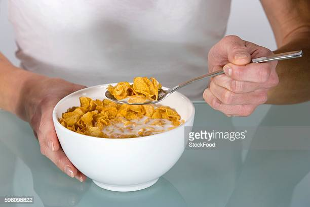 A woman eating cornflakes with milk