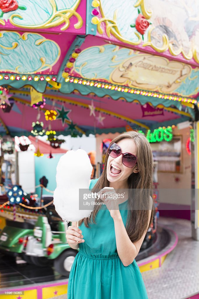 Woman eating cotton candy at fair : Stock Photo