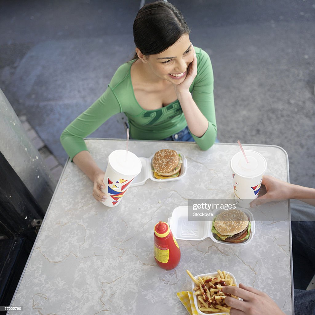 Woman eating fast food outdoors, high angle view : Stock Photo