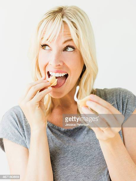Woman eating fortune cookie, studio shot